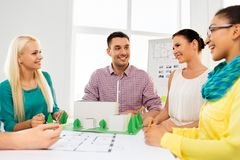 Creative team with blueprint working at office. Architecture , construction and people concept - creative team of architects or designers with project blueprint royalty free stock photo