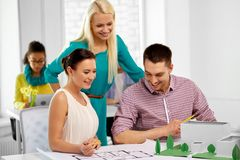 Creative team with blueprint working at office. Architecture , construction and people concept - creative team of architects or designers with project blueprint stock image
