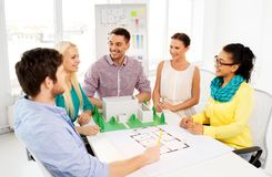 Creative team with blueprint working at office. Architecture , construction and people concept - creative team of architects or designers with project blueprint stock images