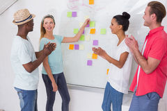 Creative team clapping hands by sticky notes on wall Stock Image