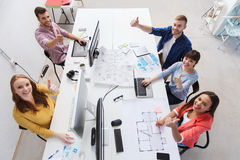 Creative team with computers showing thumbs up Royalty Free Stock Photos