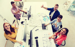 Creative team with computers showing thumbs up. Business, startup, success and people concept - creative team with computers, blueprint and scheme showing thumbs Royalty Free Stock Image