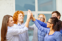 Creative team doing high five gesture in office Royalty Free Stock Image
