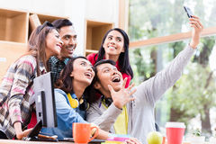 Creative team of five enthusiastic employees making a selfie photo. With the mobile phone in the office royalty free stock image