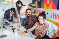 Creative team of four colleagues working in modern office Stock Images