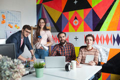 Creative team of four colleagues working in modern office Stock Photo