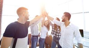 Creative team giving each other a high five. The concept of teamwork stock photos