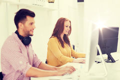 Creative team with headphones and computer. Business, startup, education, technology and people concept - happy creative team or students with headphones and Stock Photos