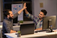 Creative team making high five at night office Royalty Free Stock Image