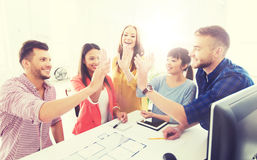Creative team making high five at office Stock Images