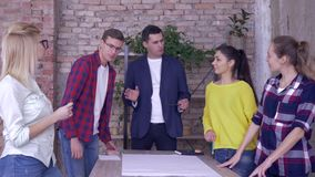 Creative team in modern office, Successful corporate executive guy with collaborators working on development project of. New business ideas on big drawing paper stock video
