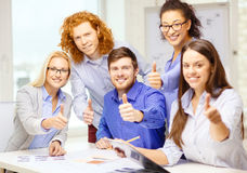 Creative team with papers showing thumbs up Stock Image