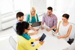 Creative team with table computers in office. Business, technology and startup concept - happy creative team with table pc computer at office stock image