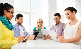 Creative team with table computers in office. Business, technology and startup concept - happy creative team with table pc computer at office stock images