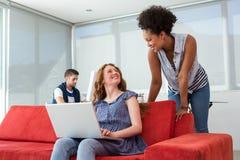 Creative team using laptop on sofa Royalty Free Stock Photo