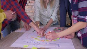 Creative teamwork, hands of office employees close up make up new project development business idea on big paper with stock footage