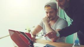 Creative teamwork workflow in agency / office. Creative workflow in start up agency, worker explain project on laptop screen - instagram style analog film look stock video