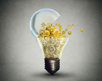 Creative technology communication concept lightbulb with gears. Creative technology and communication concept as an open door light bulb transferring gears and Royalty Free Stock Image