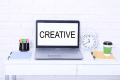 Creative. Text on monitor. Modern workplace with computer, cup of coffee and clock. Mock up and copy space stock images