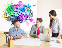 Creative thinking concept. Attractive young businesspeople working on project together in modern office with colorful brain sketch. Creative thinking concept Stock Photo
