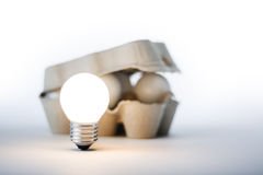 Thinking Outside The Box. Creative thinking concept. An egg box containing light bulbs but with one outside and switched on. With white copy space stock image