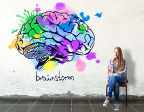 Creative thinking concept. Thoughful european girl sitting on chair in concrete room with bright human brain sketch on wall. Creative thinking concept. 3D Royalty Free Stock Photography
