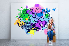 Creative thinking concept. Young woman sitting in concrete room with colorful brain sketch on banner. Creative thinking concept. 3D Rendering Stock Image