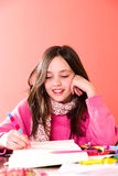 Creative time. Young happy schoolgirl drawing with a colorful pencil Stock Photo
