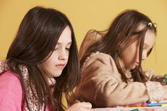 Creative time. Two young schoolgirls drawing together Stock Image