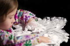 Creative Toddler Playing with White Foam. Little girl enjoying playing with foamy cream Royalty Free Stock Photography