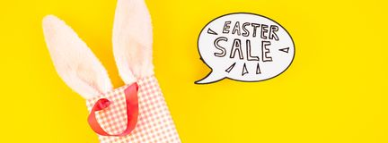 Creative Top view holiday Easter Sale Concept. Creative Top view flat lay holiday promo composition Easter sale bunny ears eggs text message on bold yellow paper stock image