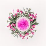 Creative tropical composing with exotic flowers, palm leaves and pink party paper fan on white background, top view. stock photography
