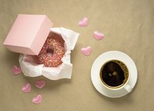 Love at first bite. Creative valentine concept photo of donut with coffee cup on brown background Royalty Free Stock Photos