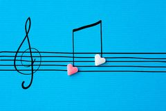 Creative Valentine greeting card. Sugar heart shape candies hand drawn doodle sketch musical notes on staff treble clef on blue