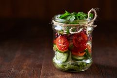 Creative vegetable salad served in glass jar over dark wooden background, selective focus, shallow depth of field. Creative fresh vegetable salad served in stock images