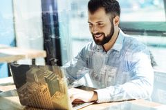 Handsome beardful man working with computer and focusing on it. Creative vision. Adult perspective beardful employer working with computer sitting and smiling Stock Image