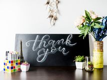 Creative White and blue Chalk Lettering Thank you on chalkboard on table with plants, flowers and art objects in home interior. Th. Anksgiving, holiday concept Stock Photography