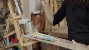 Creative woman is drawing image in artistic studio. Painter woman is painting a picture in workshop. She is sitting in front of easel, taking dye from palette stock video footage