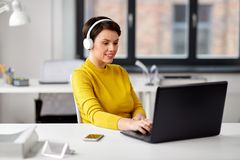 Creative woman in headphones with laptop at office royalty free stock photo