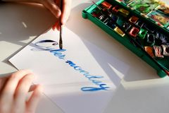 Female calligrapher creates inscription for sale, using brushes stock photos