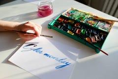 Female calligrapher creates inscription for sale, using brushes royalty free stock image