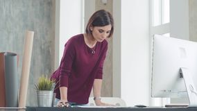 Creative Woman is an interior designer, working on the project. Creative Woman standing near at desk in a Light and Modern Office. She is an interior designer stock video