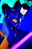 Blue neon make up. Creative woman model shine blue green orange colors. Bright conceptual art make-up glows under ultraviolet light. Club disco neon party time Royalty Free Stock Photo