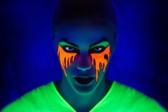 Blue neon make up. Creative woman model shine blue green orange colors. Bright conceptual art make-up glows under ultraviolet light. Club disco neon party time Royalty Free Stock Photos