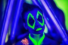 Halloween neon art. Creative woman model shine blue green orange colors. Bright conceptual art make-up glows under ultraviolet light. Club disco neon party time Stock Photo