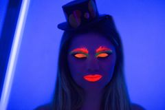 Halloween neon art. Creative woman model shine blue green orange colors. Bright conceptual art make-up glows under ultraviolet light. Club disco neon party time Stock Photography