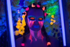 Halloween neon art. Creative woman model shine blue green orange colors. Bright conceptual art make-up glows under ultraviolet light. Club disco neon party time Royalty Free Stock Images