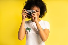 Creative woman-photographer takes photos, isolated on yellow. stock photography