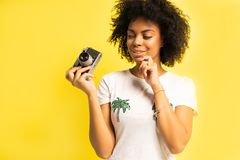 Creative woman-photographer takes photos, isolated on yellow. royalty free stock photography