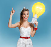 Creative woman showing light bulb banner looking happy excited Royalty Free Stock Photo
